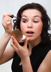 Woman is applying mascara while looking in mirror