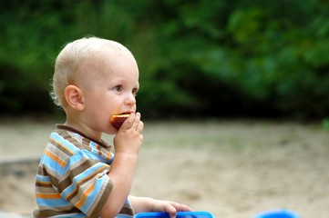 Cute blond child eating some fruits