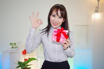 プレゼントを持ったガッツポーズの女性