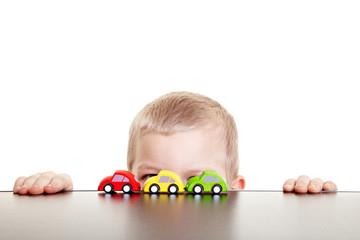 Kind versteckt sich hinter Spielzeugautos
