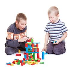 Zwei Geschwister spielen mit Holzklötzen