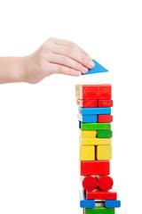 Hand stellt Baustein auf Turm