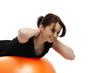 junge hübsche frau trainiert mit einem orangenen gymnastikball