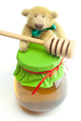 teddy bear ,stick to hohey  and  jar of honey  isolated on white