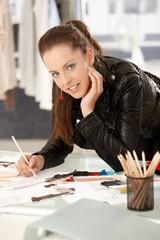 Pretty young fashion designer working in studio