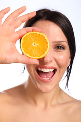 Excited beautiful young woman with orange fruit