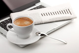 Cappuccino cup with laptop and newspaper