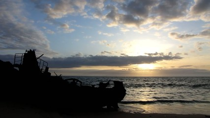 Silhouette of a stranded boat in the beach at sunset