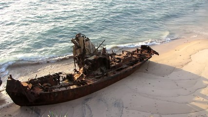 Rusty stranded boat lying in a desert beach
