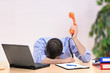 Exhausted businessman with face down holding a telephone