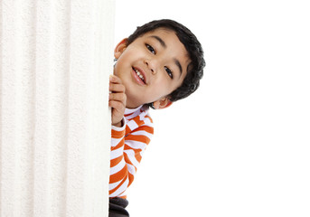 Smiling Toddler Peeks from Behind a Column, Isolated, White