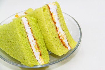 A slice of sponge Pandan cake on white background