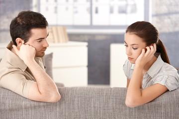 Young couple sitting on sofa sadly