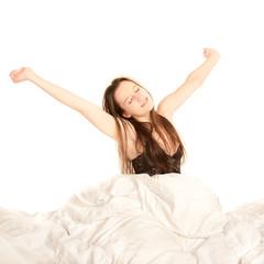 Junge Frau streckt sich und gähnt im Bett