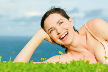 Beautiful happy laughing woman lying in green grass