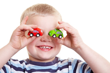 Kind hält Autos vor die Augen