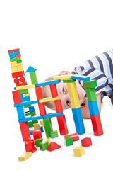 Kind schaut durch Turm aus Bausteinen