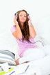 Woman relaxing on couch and listening music in headphones.