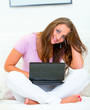 Smiling pretty woman sitting on couch and using laptop.