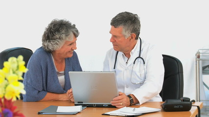 Woman looking at the laptop of her doctor