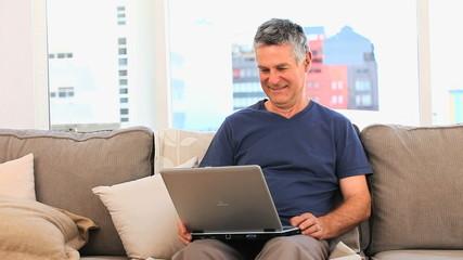 Mature man looking at  his laptop