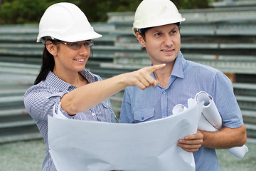 young engineer woman shows her co-worker around the on site