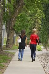 Friends Walking On The Sidewalk