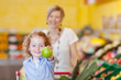 lachendes kind zeigt apfel im supermarkt