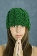 Teen girl wearing knit hat, hands clasped, portrait