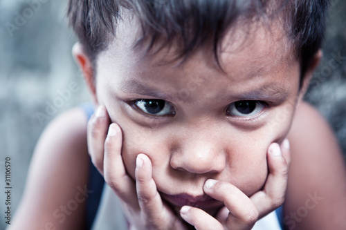 Asian boy portrait - sad with hands on face - shallow focus