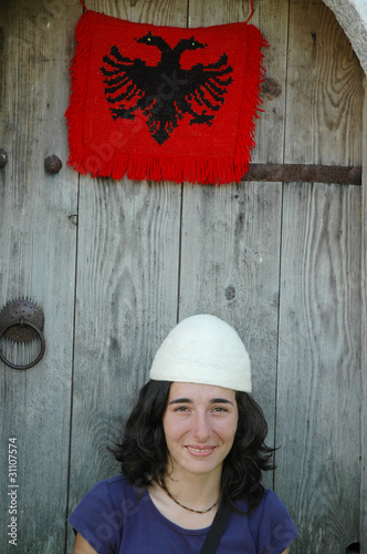 Albanian girl with traditional hat and flag of Albania