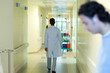 Male doctor walking in hospital corridor, full length, rear view, man in foreground
