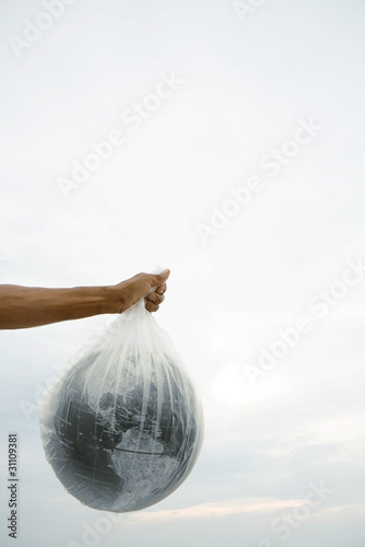 Man holding globe in plastic bag, cropped view
