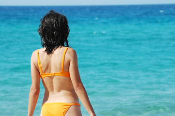 Woman in orange bikini on the beach