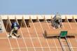 Deux couvreurs sur une toiture