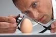 Arzt untersucht Ei mit Stethoskop auf gesundheitliche Risiken