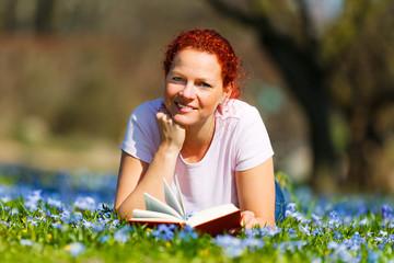 frau liest ein buch auf einer blumenwiese