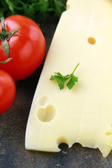 large piece of cheese varieties Maasdam  and tomato