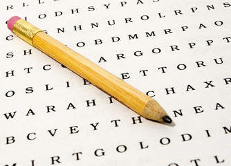 Close up of a a word search puzzle with pencil on white