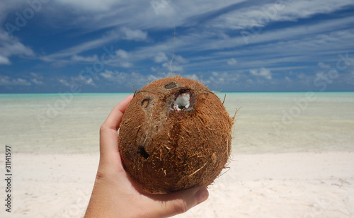 Hand holding a coconut on a tropical beach