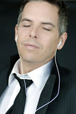 Serene Businessman With Eyes Closed Wearing Headphones poster