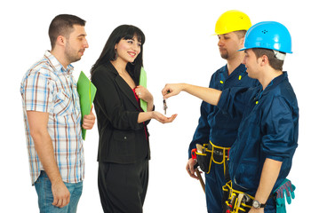 Workers giving keys to couple