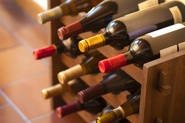 Red and white wine bottles stacked on wooden racks