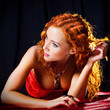 Sexy girl with red hair wearing  amber jewellery on black