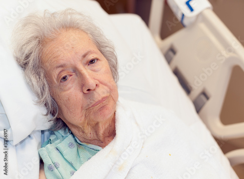 Elderly 80 year old woman with Alzheimer in a hospital bed