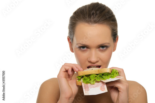 Woman biting a sandwich out of money and lettuce