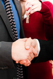 Couple receiving keys from real estate broker poster