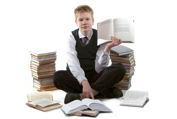 schoolboy in school uniform sits on floor,near to packs of books