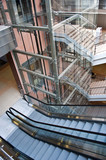 Glass lift shafts and escalators in a modern office building poster