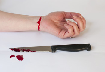 A suicidal womans wrist with blooded knife after suicide attempt